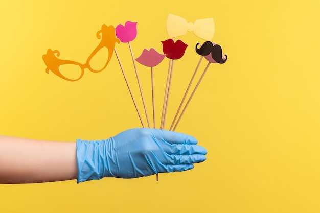 Human hand in blue surgical gloves holding and showing many different stick photo-booth in hand