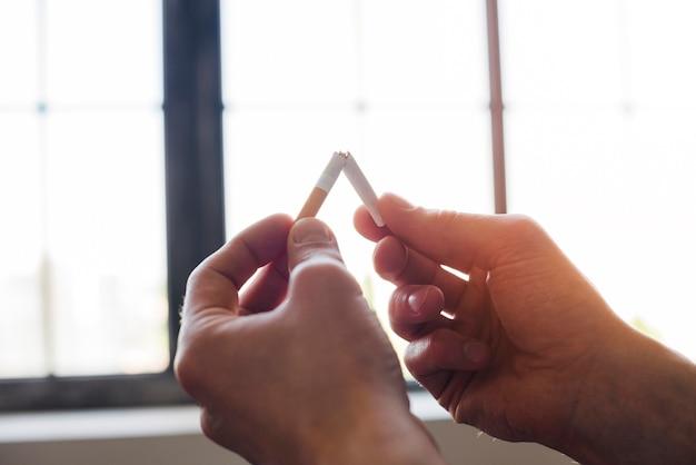 Человеческая рука ломает сигарету перед окном