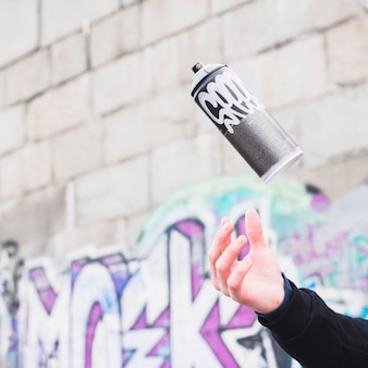Human hand catching spray can