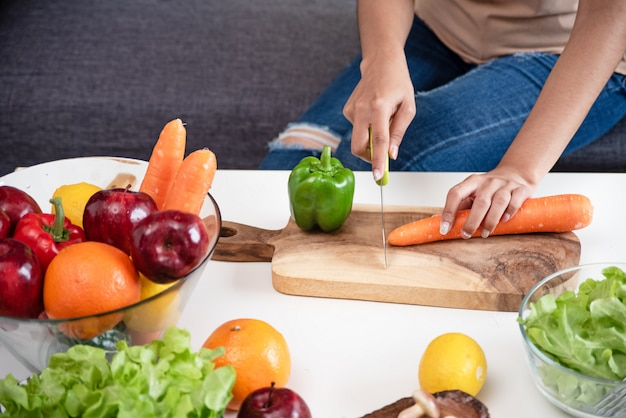 Human hand cutting carrot on wooden tray, fresh vegetable was preparing for salad meal