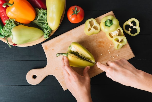 Human hand cutting green bell pepper on wooden chopping board