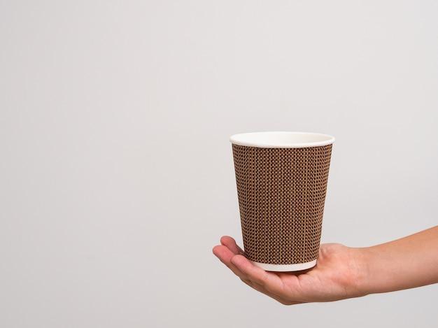 人間の手は、コーヒーツーゴーの背景に段ボールのテクスチャガラスを保持します。