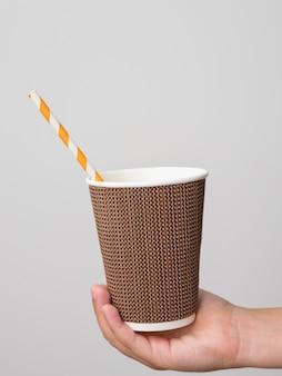 人間の手が飲むチューブでコーヒーツーゴーの段ボールテクスチャガラスを保持します。