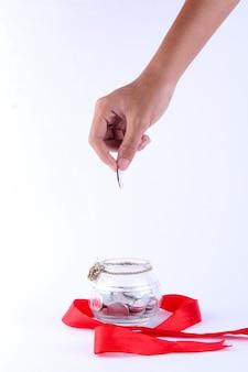 Человеческая рука держит монету в прозрачной банке и украшена красной лентой вокруг нее