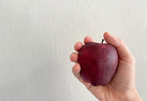 인간의 손을 잡고 복사 공간 벽으로 빨간색 잘 익은 사과.