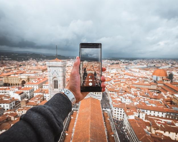 Человеческая рука держит смартфон, чтобы сфотографировать флоренцию