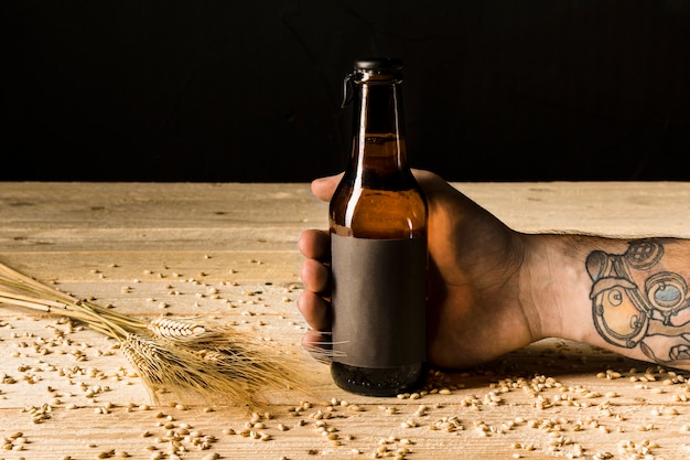 Human hand holding alcoholic bottle with ears of wheat on wooden surface