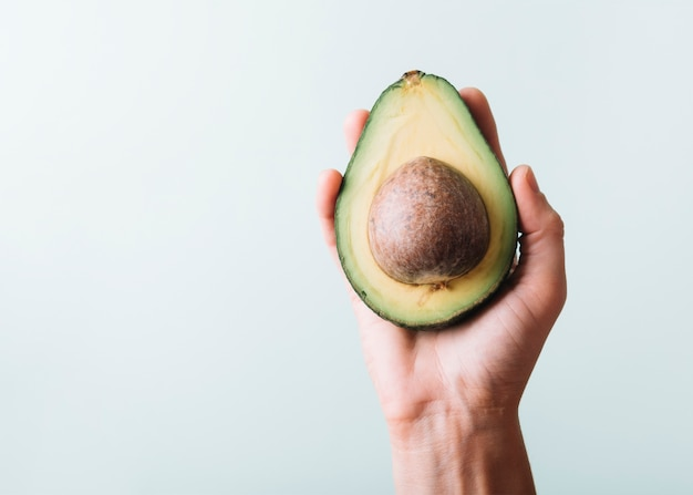 Human hand holding avocado on green background