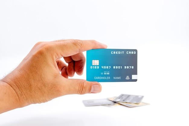 白い背景の上の銀行のクレジットカードを保持している人間の手。