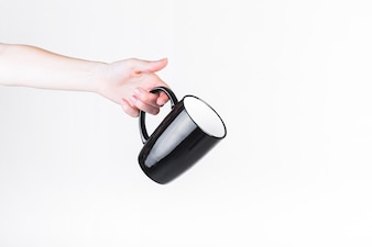 Human hand holding black cup on white backdrop
