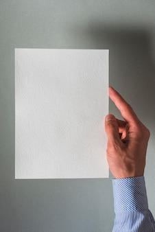 Mano umana che tiene carta bianca vuota