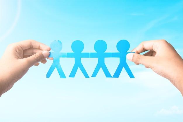 Человеческая рука держит голубую бумагу людей, взявшись за руки на фоне голубого неба. концепция всемирного дня народонаселения