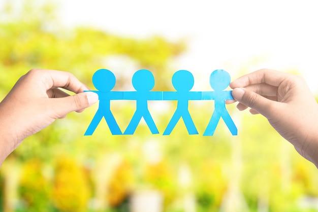 Человеческая рука, держащая синих людей бумагу, держась за руки с размытым фоном. концепция всемирного дня народонаселения