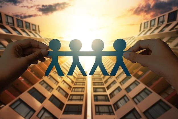 Человеческая рука держит голубую бумагу людей, взявшись за руки с фоном городских пейзажей. концепция всемирного дня народонаселения