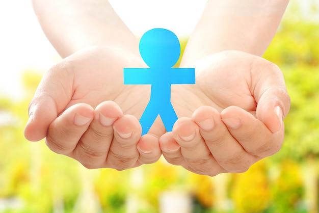 Человеческая рука держит бумагу синих людей с размытым фоном. концепция всемирного дня народонаселения