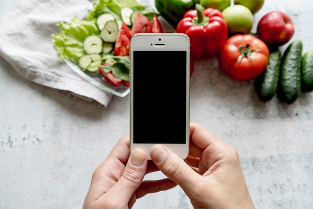 Human hand holding cellphone over organic vegetables on concrete backdrop