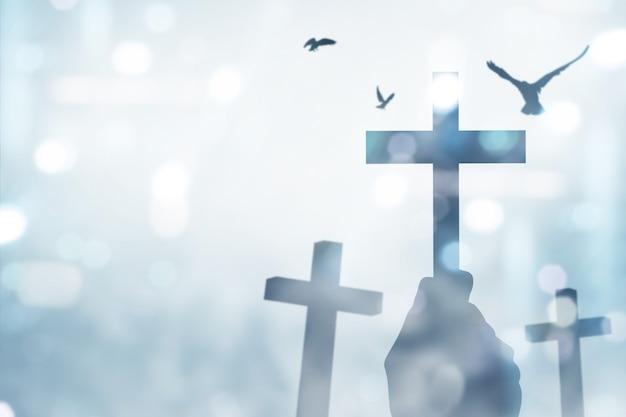 인간의 손을 잡고 기독교 십자가와 흐린 빛을 배경으로 비행 비둘기
