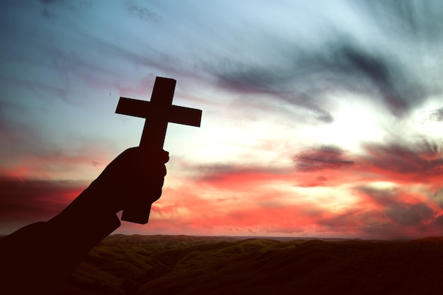 인간의 손에 일몰 하늘 배경으로 기독교 십자가 들고