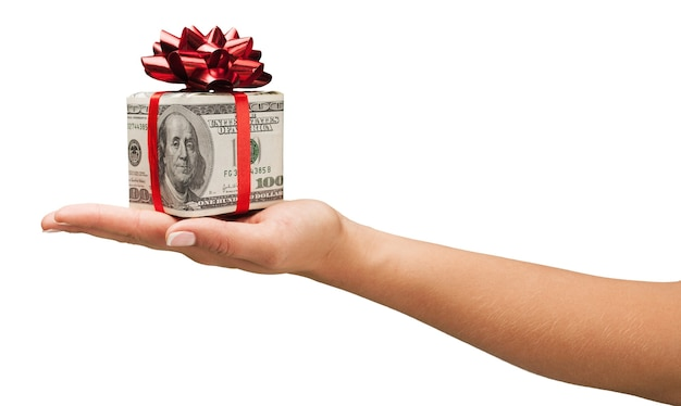 Human hand holding christmas present wrapped in dollar banknotes isolated on white