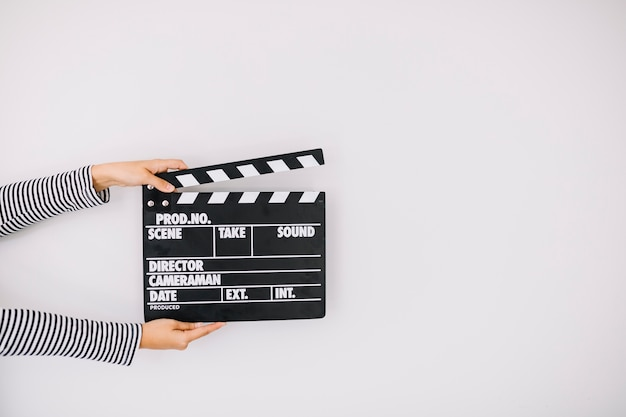 Human hand holding clapper board on white background