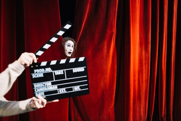 Human hand holding clapperboard in front of male mime artist face