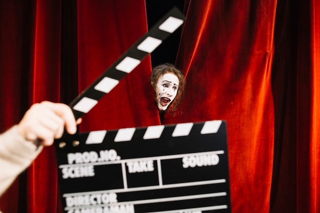 Human hand holding clapperboard in front of male mime artist performing behind red curtain