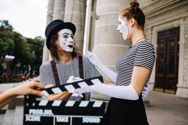 Human hand holding clapperboard in front of surprised female mime looking at male mime
