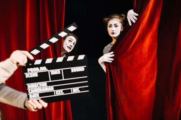 Human hand holding clapperboard in front of two mime artist performing on stage