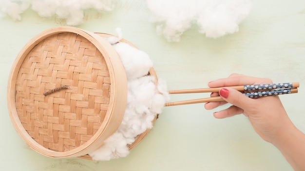 Human hand holding cotton with chopsticks from steamer