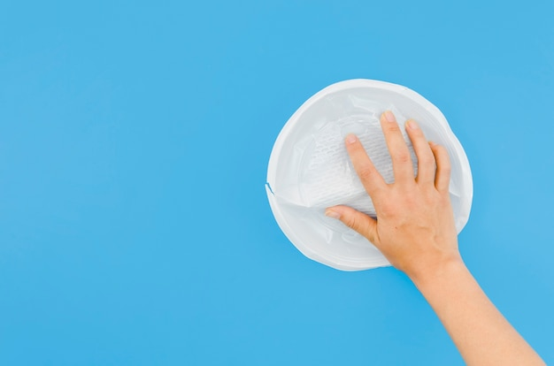 Human hand holding crumpled plastic plate on blue surface