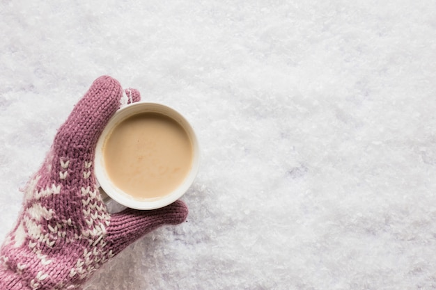 Human hand holding cup of coffee over the snowy land