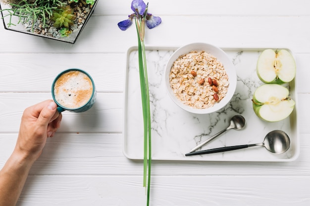 Human hand holding a cup of coffee with delicious breakfast on wooden plank