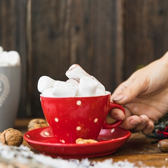 Human hand holding cup with marshmallow