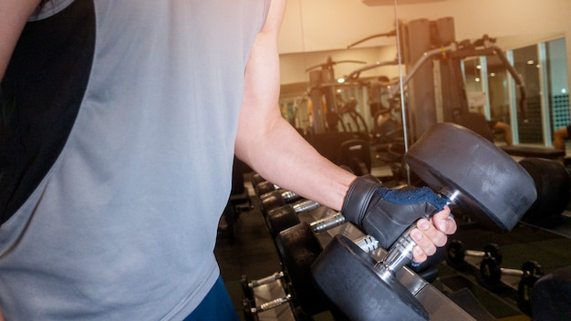 Human hand holding dumbbell in gym