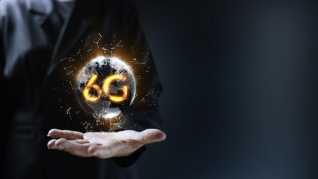 地球6g地球ホログラフィック技術を保持している人間の手。バーチャルリアリティと拡張現実の未来的な視覚化。テキスト用の空きスペース。