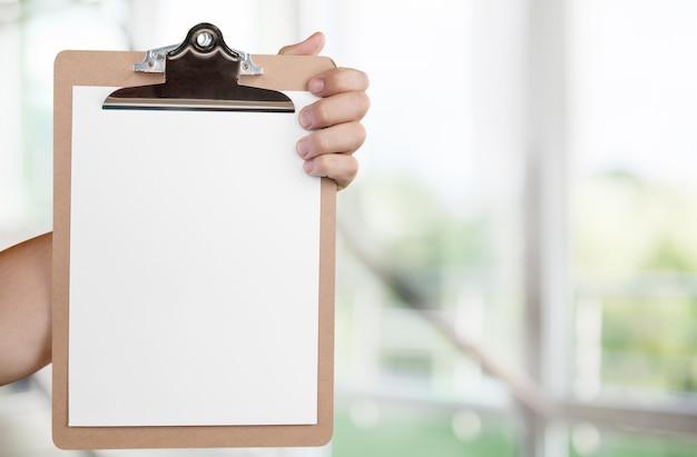 Человеческая рука, держащая папку с белым чистым листом бумаги
