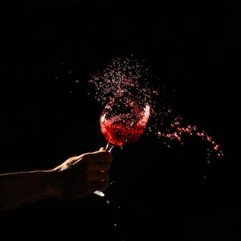 Human hand holding glass of red wine splashing out