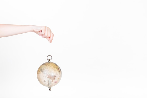 Human hand holding globe pendulum