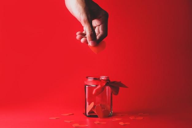 Человеческая рука держит символ сердца, чтобы положить в прозрачную банку, украшенную красной лентой