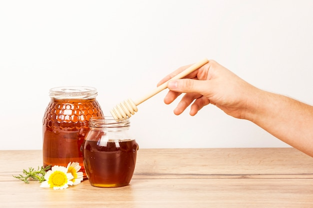 Human hand holding honey dipper from honey jar