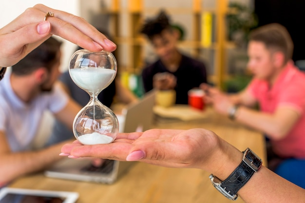 Human hand holding hourglass in front of people at background