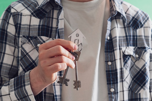 A human hand holding a key from home symbol of apartment real estate purchase