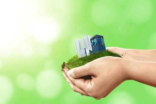 Человеческая рука, держащая землю со зданиями и квартирами. всемирный день хабитат