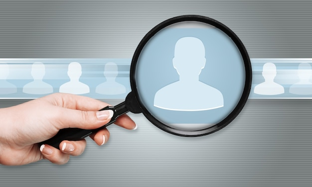 Human hand holding magnifying glass searching people icons on background