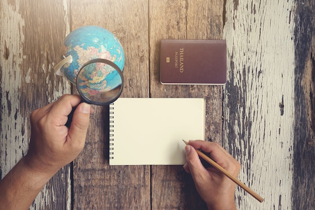 Человеческая рука с увеличительным стеклом на земном шаре в поисках путешествия