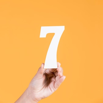 黄色の背景に対して数7を持っている人間の手