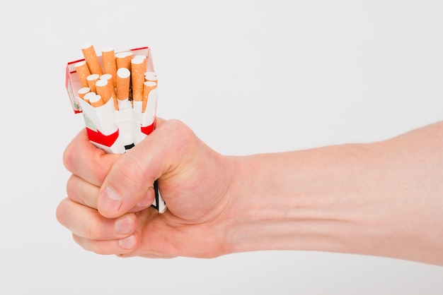 Human hand holding packet of cigarettes