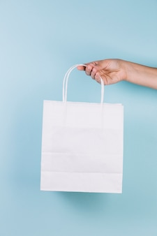 Human hand holding paper shopping bag
