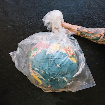 Human hand holding plastic bag with globe