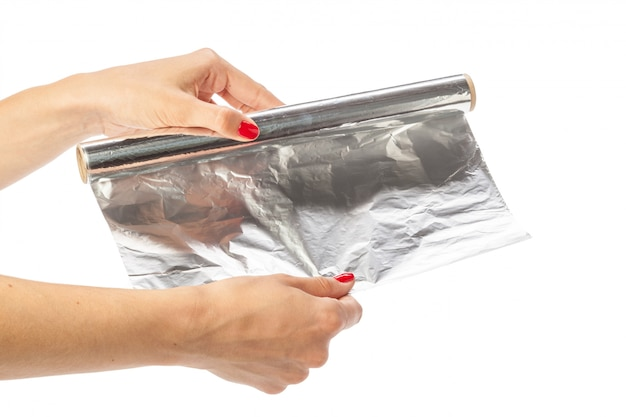 Human hand holding a roll of foil on a white